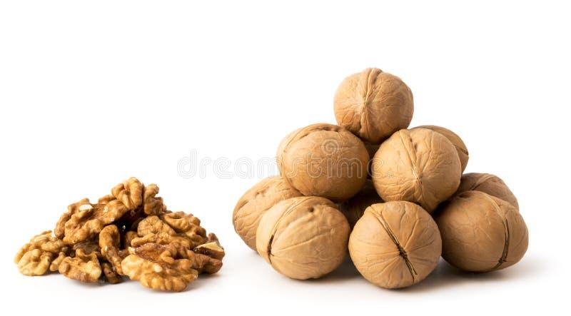 Un groupe de noix dans une peau et un groupe d'éplucher sur un blanc, d'isolement images stock