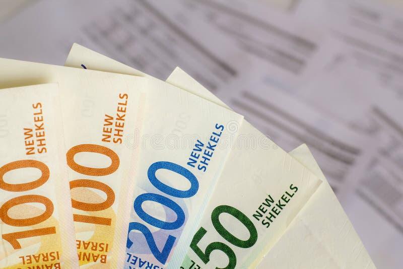 Un groupe de nouveaux billets de banque israéliens de shekel dans la main sur le fond de factures images libres de droits