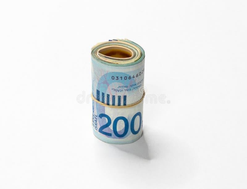 Un groupe de nouvelles notes israéliennes d'argent des shekels NIS s'est enroulé et lié avec une bande élastique simple sur un ba image stock