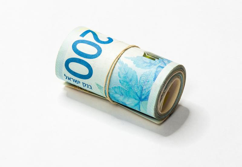 Un groupe de nouvelles notes israéliennes d'argent des shekels NIS s'est enroulé et lié avec une bande élastique simple sur un ba image libre de droits