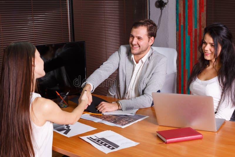 Un groupe de personnes à une entrevue, l'homme serre la main à une fille indoors photographie stock libre de droits