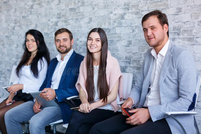 Un groupe de personnes heureuses, séance et sourire, tenant des téléphones portables et un comprimé indoors photos stock