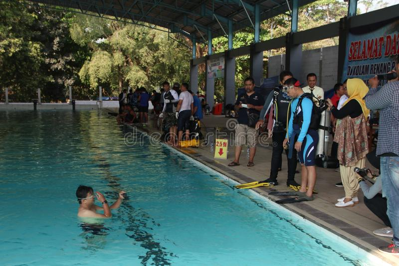 Un groupe de personnes s'entraînant à la plongée dans une piscine photographie stock