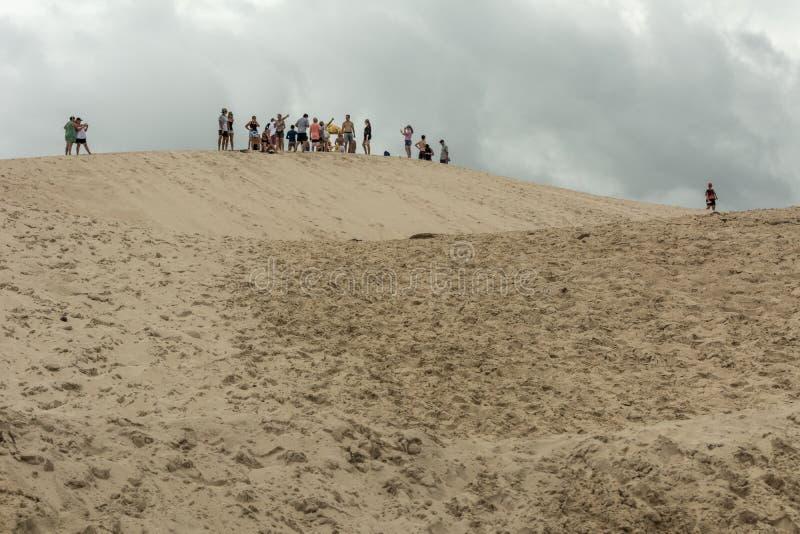 Un groupe de personnes sur le dessus d'une montagne de sable sur un secteur de dunes en Joaquina Beach, Florianopolis, Brésil image libre de droits