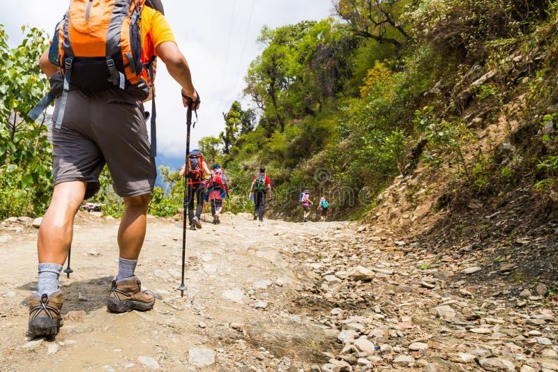 Un groupe de personnes trekking sur le chemin de terre au Népal photographie stock libre de droits