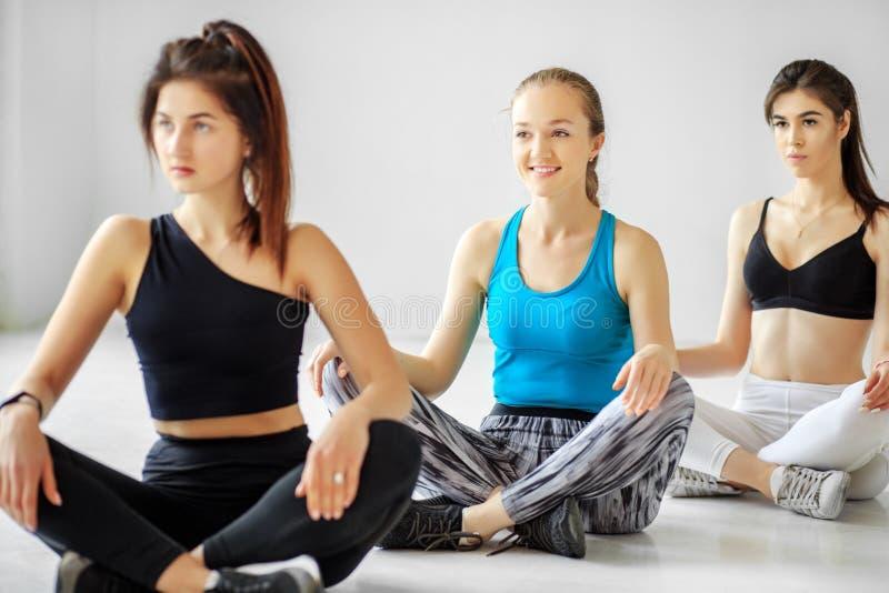 Un groupe de personnes de yoga est engagé dans la formation dans le gymnase Le concept des sports, mode de vie sain, forme physiq photo stock