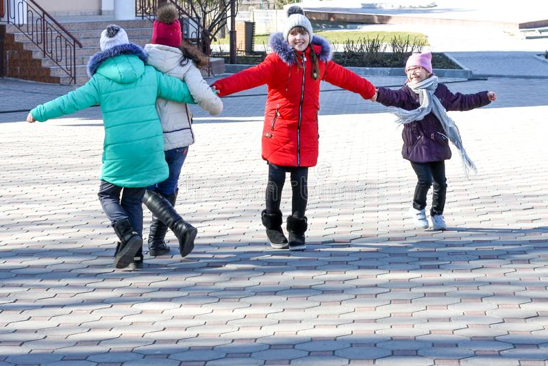 Un groupe de quatre adolescentes heureuses un jour ensoleillé dupant autour dans la cour images stock