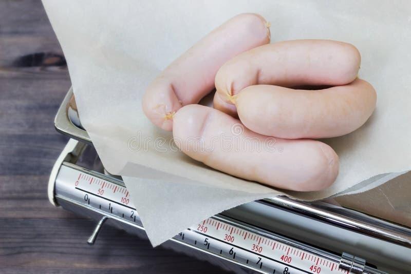 Un groupe de saucisses dans la boucherie sur le papier parcheminé blanc sur les vieilles échelles de cuisine de vintage Saucisse  image stock