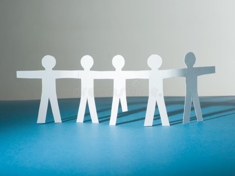 Un groupe de silhouettes de papier de personnes se tiennent ensemble L'un d'entre eux sans jambes photos stock