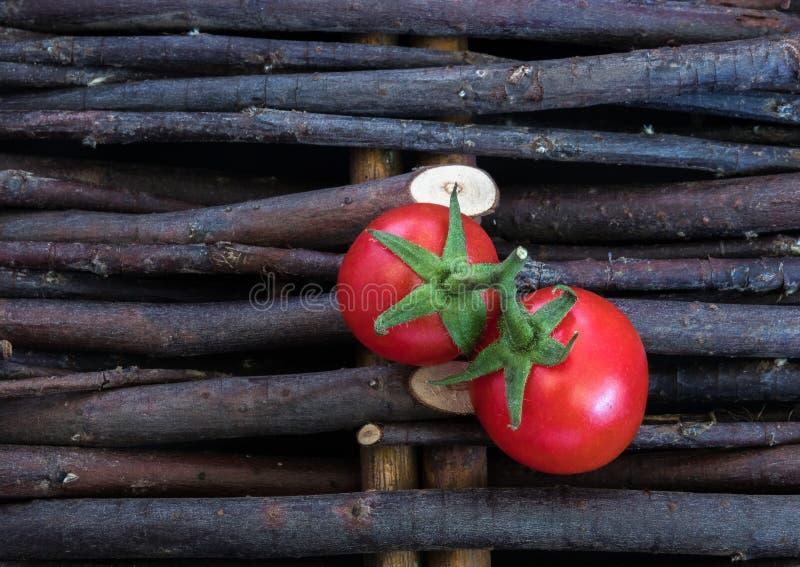 Un groupe de tomates sur un fond en osier de tiges Dans un style rustique Petites tomates-cerises rouges photographie stock