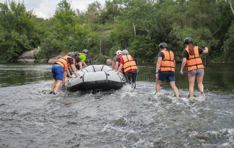 Un groupe de touristes mène le bateau sur une petite section de la rivière pendant transporter photos stock