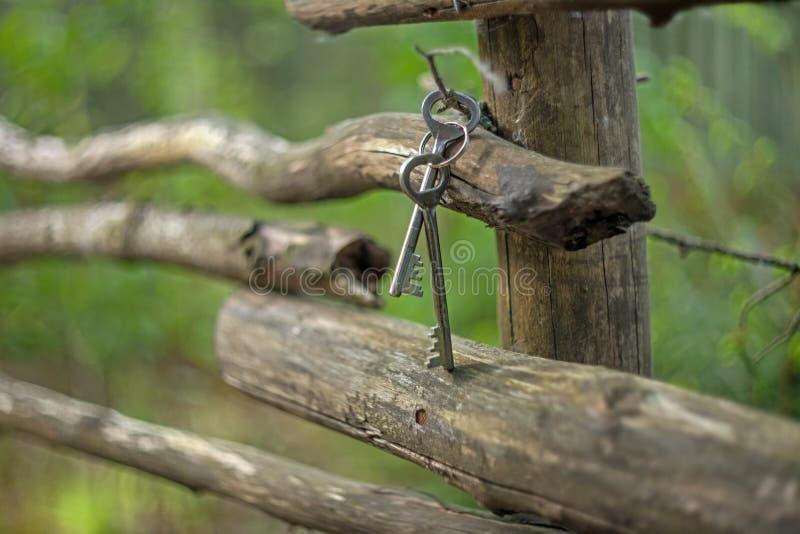Un groupe de vieilles clés de porte de fer de cru accrochant sur une vieille barrière rustique des poteaux tordus avec un fond br photo stock