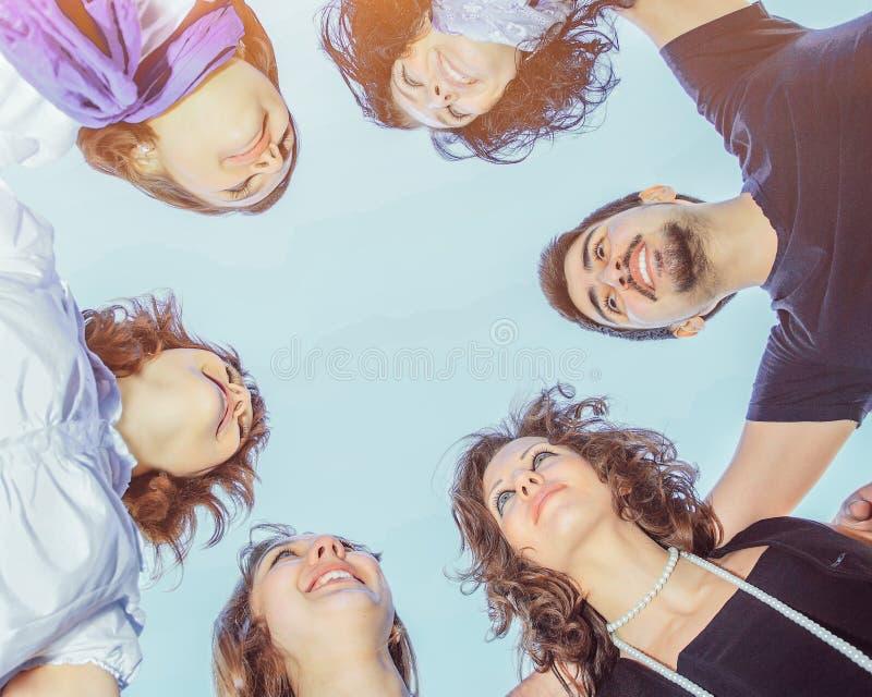 Un groupe des jeunes en cercle sur le ciel regardant chaque o image stock