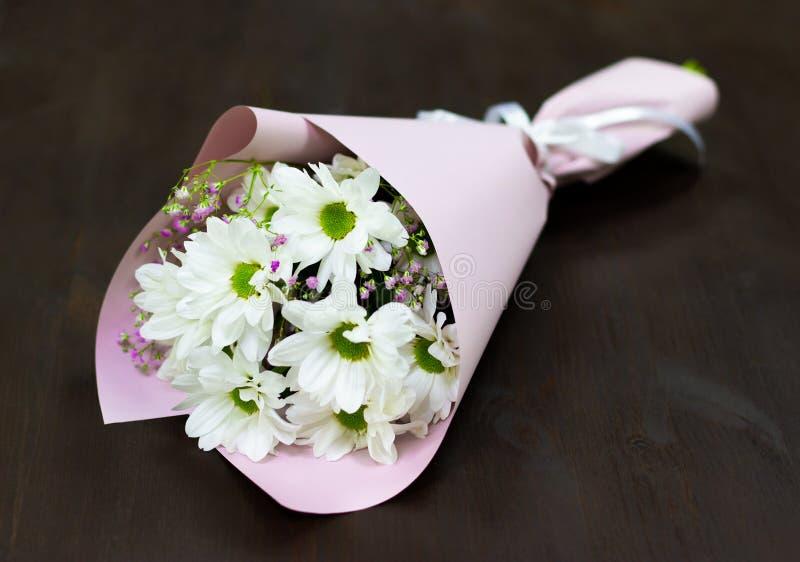 Un groupe frais de marguerites blanches se trouve sur un fond floral naturel de conseil en bois photos stock