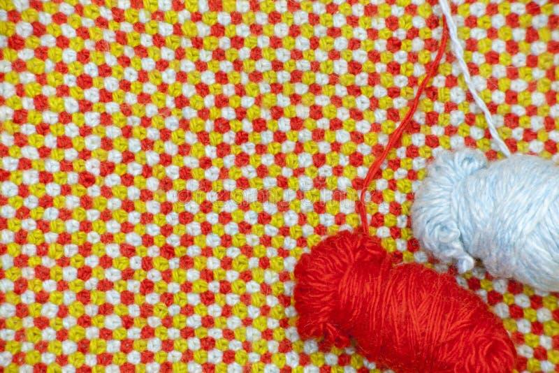 Un groviglio dei filati rossi e blu su un fondo del panno tricottato con lana rossa, blu e verde fotografia stock