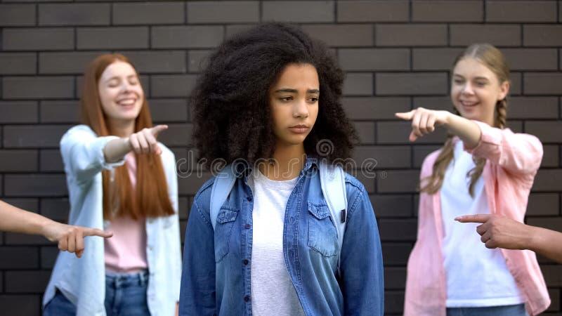 Un grupo cruel de adolescentes apuntando con el dedo a una escolar afro-americana, racismo imagen de archivo