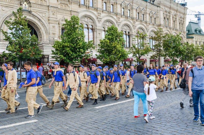 Un grupo de adolescente-turistas en el uniforme del campamento de verano va en pares en el cuadrado rojo foto de archivo libre de regalías