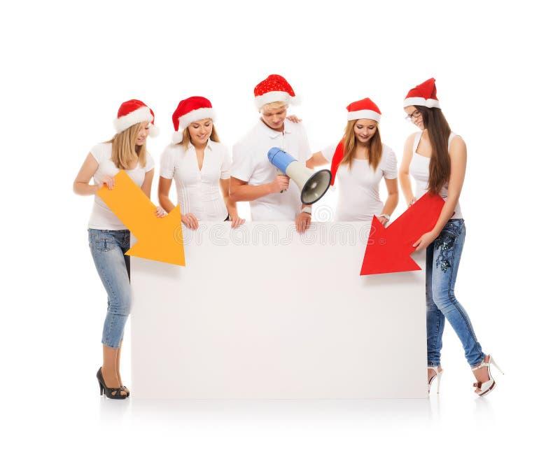 Un grupo de adolescentes en sombreros de la Navidad que señalan en un banne en blanco fotos de archivo libres de regalías