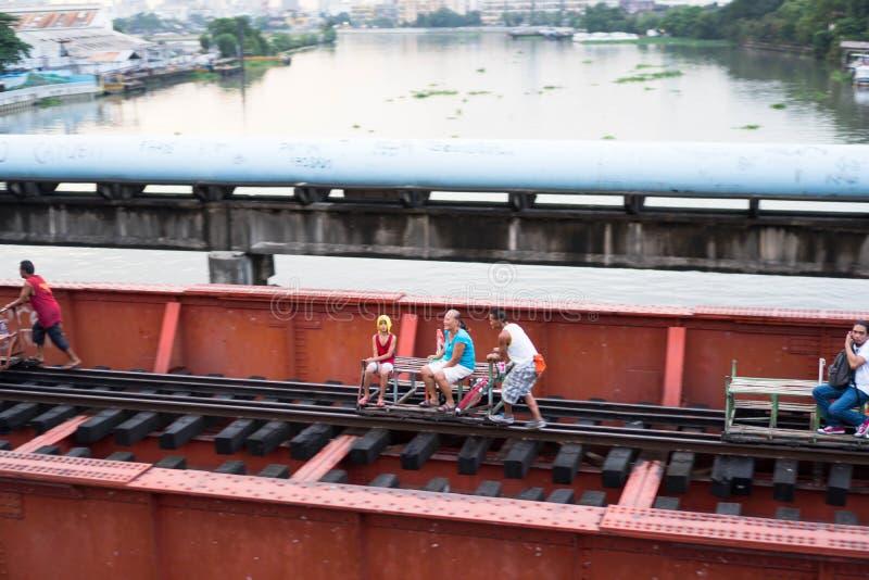 Un grupo de adolescentes que usan un ferrocarril viejo para transportar a una gente manualmente fotografía de archivo
