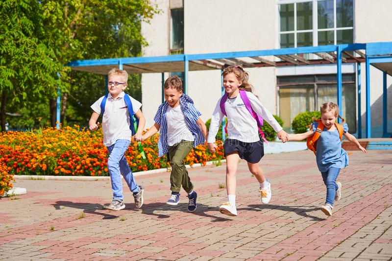 Un grupo de alumnos que corren extraescolar, llevando a cabo las manos de cada uno fotografía de archivo libre de regalías