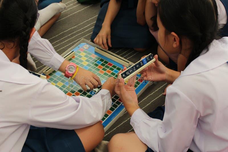 Un grupo de alumnos que juegan el Scrabble de la matemáticas fotos de archivo libres de regalías
