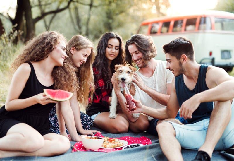 Un grupo de amigos con un perro que se sienta en la tierra en un roadtrip a través de campo imágenes de archivo libres de regalías