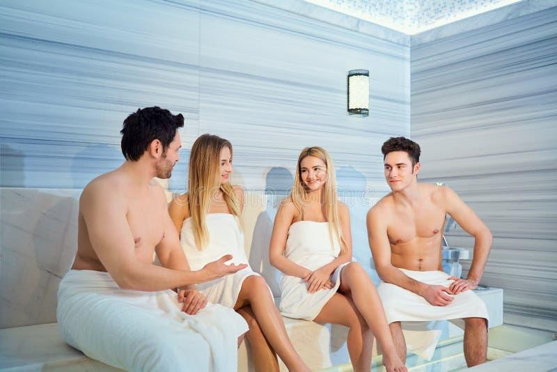 Un grupo de amigos en las toallas se ríe de la sauna fotografía de archivo