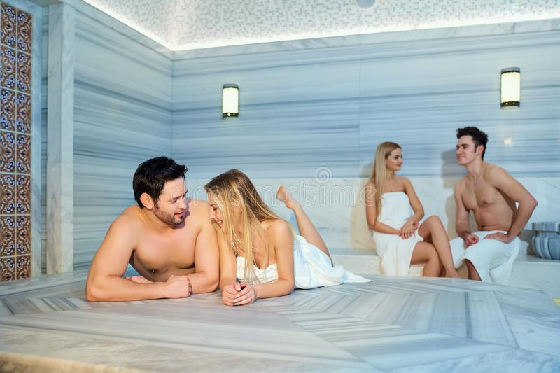 Un grupo de amigos en las toallas se ríe de la sauna imagen de archivo libre de regalías