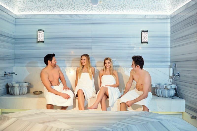 Un grupo de amigos en las toallas se ríe de la sauna fotos de archivo