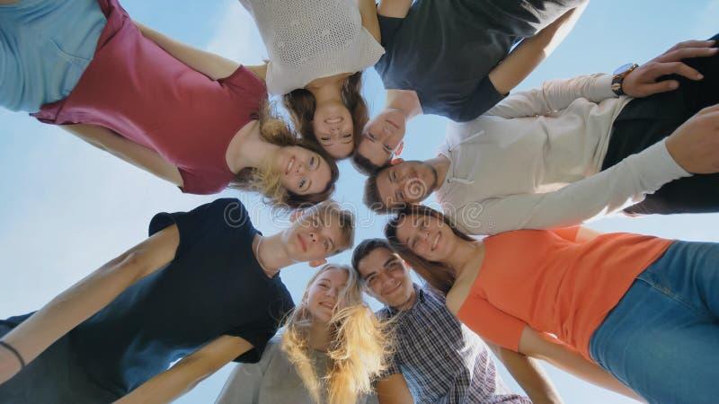 Un grupo de amigos de estudiantes mira abajo y agita sus manos fotos de archivo