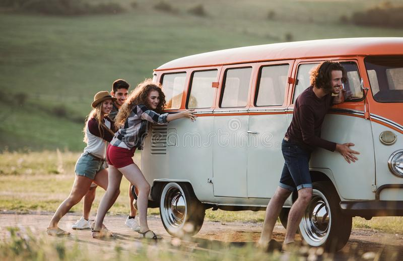 Un grupo de amigos jovenes que empujan un coche quebrado en un roadtrip a través de campo fotos de archivo libres de regalías