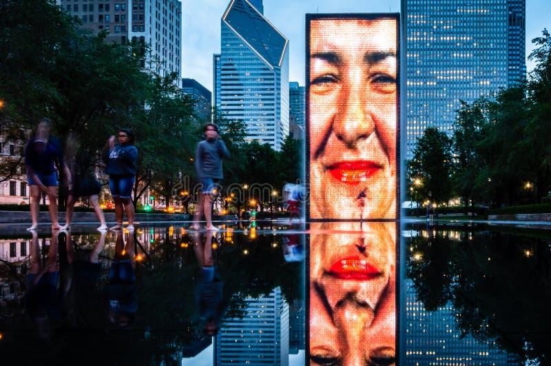 Un grupo de amigos jovenes que juegan y que animan en el parque Piscina de reflejo del agua en el parque del milenio, Chicago foto de archivo libre de regalías