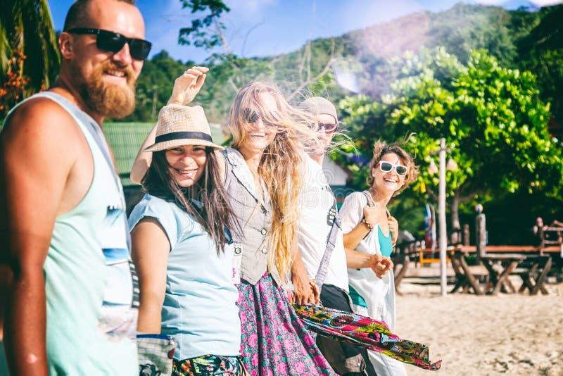 Un grupo de amigos de la gente joven 30 años camina en la playa, happ imágenes de archivo libres de regalías