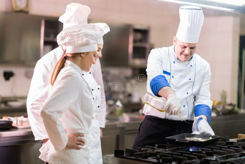 Un grupo de cocineros que preparan la comida deliciosa en alto restaurante de lujo imágenes de archivo libres de regalías