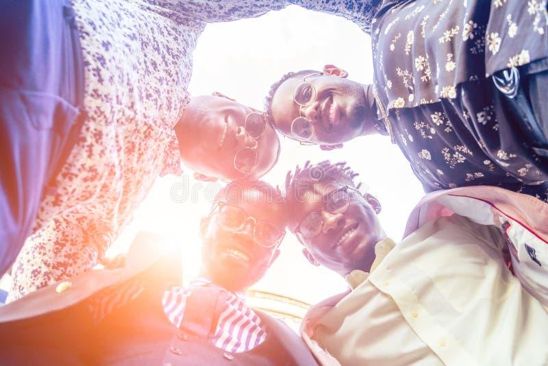 Un grupo de cuatro amigos afro americanos negros hombres de negocios con traje de negocios elegante, costoso apretón de manos con fotografía de archivo