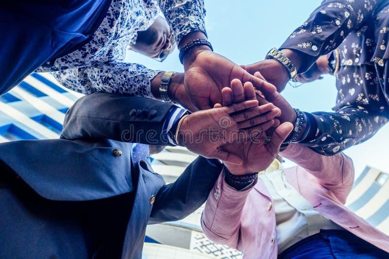 Un grupo de cuatro amigos afro americanos negros hombres de negocios con traje de negocios elegante, costoso apretón de manos con fotos de archivo