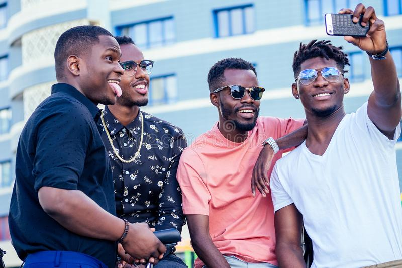 Un grupo de cuatro estudiantes afroamericanos de moda que se comunican en la calle mirando la toma de smartphones fotografía de archivo