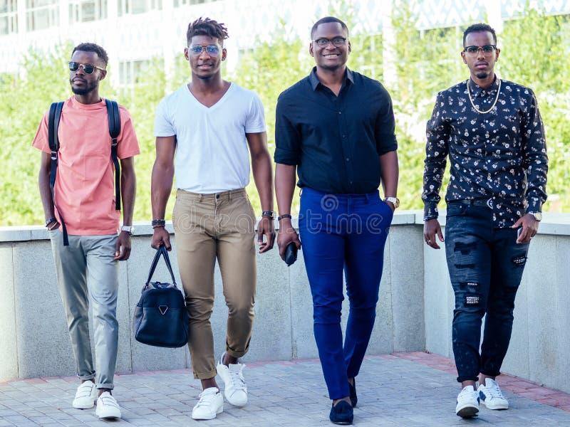 Un grupo de cuatro guapos hombres de negocios americanos caminan con estilo por el parque fotos de archivo