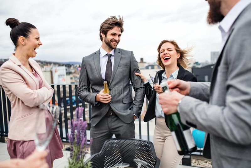 Un grupo de empresarios alegres que tienen un aire libre del partido en terraza del tejado en ciudad fotografía de archivo libre de regalías