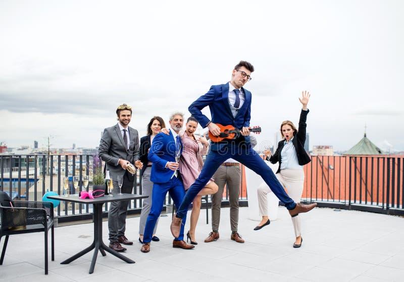 Un grupo de empresarios alegres que tienen un aire libre del partido en terraza del tejado en ciudad fotos de archivo