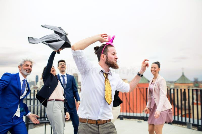 Un grupo de empresarios alegres que tienen un aire libre del partido en terraza del tejado en ciudad imagenes de archivo