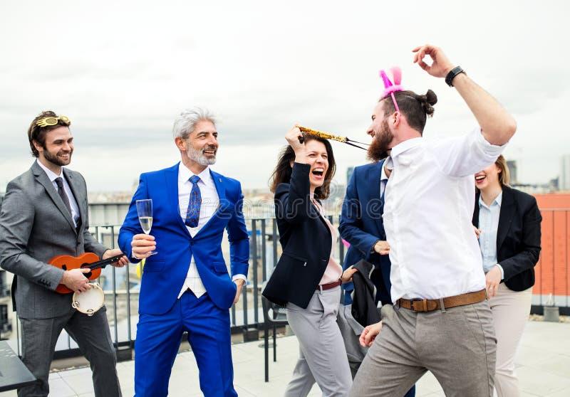 Un grupo de empresarios alegres que tienen un aire libre del partido en terraza del tejado en ciudad foto de archivo