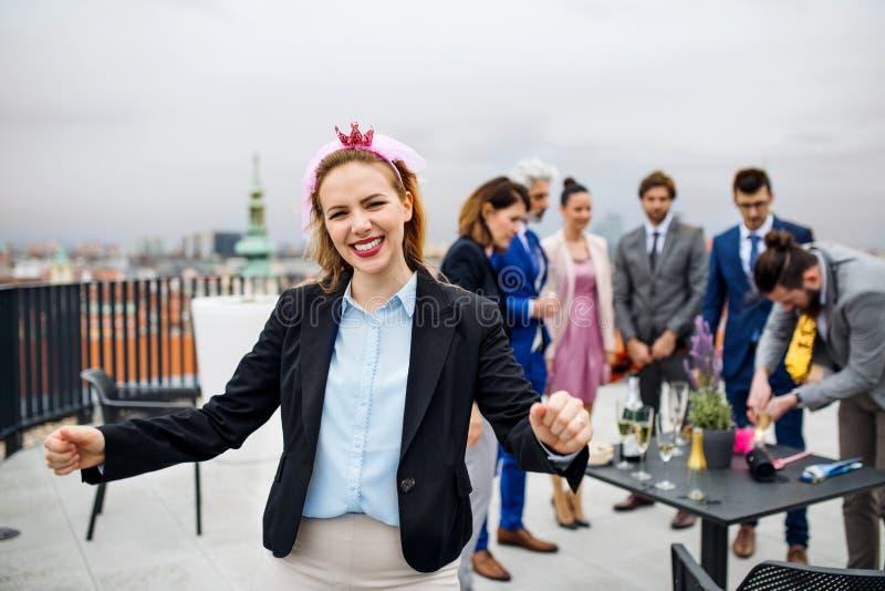 Un grupo de empresarios alegres que tienen un aire libre del partido en terraza del tejado en ciudad fotografía de archivo