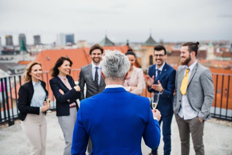 Un grupo de empresarios alegres que tienen un aire libre del partido en terraza del tejado en ciudad imagen de archivo