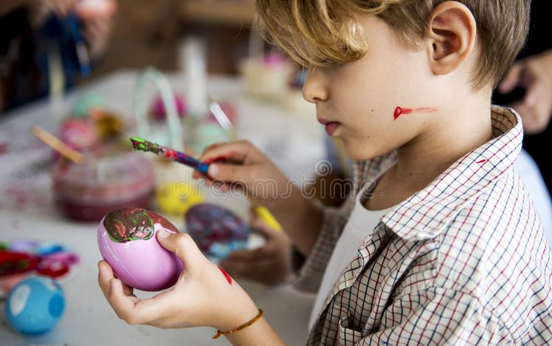 Un grupo de escolares primarios que colorean los huevos de Pascua fotografía de archivo libre de regalías