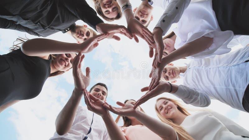 Un grupo de estudiantes de la High School secundaria mira con la forma de un círculo creado de sus palmas El concepto de amistoso imágenes de archivo libres de regalías