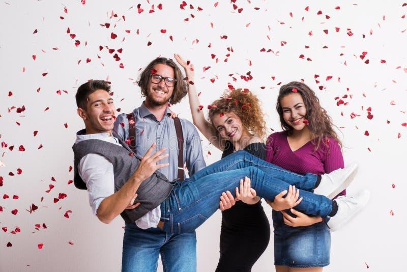 Un grupo de gente joven que detiene a un amigo en un estudio, disfrutando de un partido foto de archivo libre de regalías