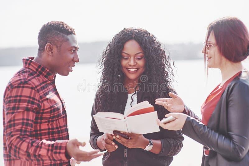 Un grupo de gente multinacional joven con un libro, estudiantes que estudian en el aire abierto fotos de archivo