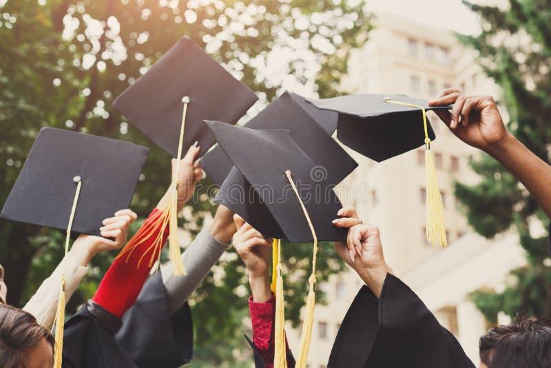 Un grupo de graduados que lanzan los casquillos de la graduación en el aire fotos de archivo libres de regalías