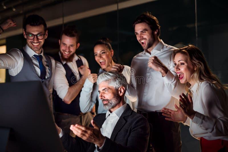 Un grupo de hombres de negocios en una oficina en la noche, expresando el entusiasmo imágenes de archivo libres de regalías
